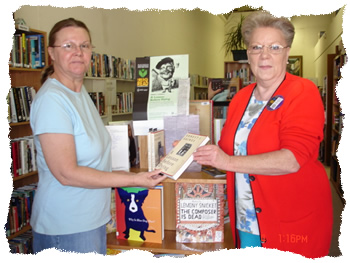 "Librarian Carol Lee tells Patron Vickie Huff about ""The Big Read"""